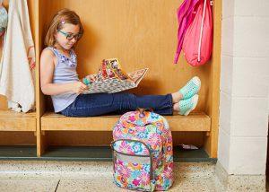 student reading yearbook in locker, blonde elementary school girl reading school yearbook