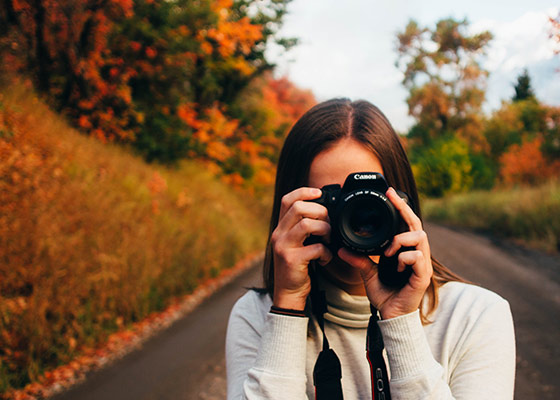 woman taking photo of fall trees changing colors